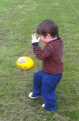 Child kicking footy