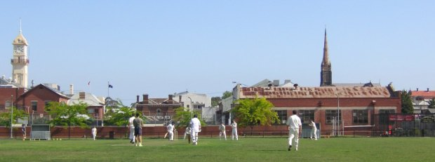 Town hall to the left, church spire to the right, cricket in the middle.
