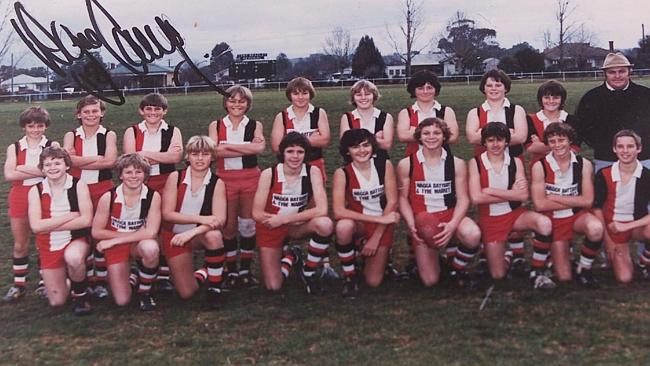 Wayne Carey: second from left, back row. Note scoreboard in the background. Image sourced from Herald Sun